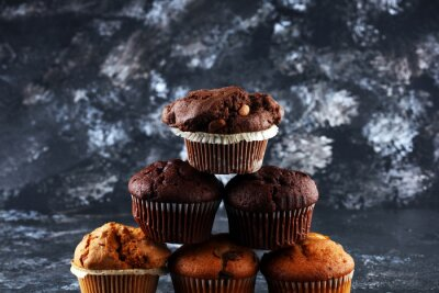 Chocolate muffin and nut muffin, homemade bakery on background.