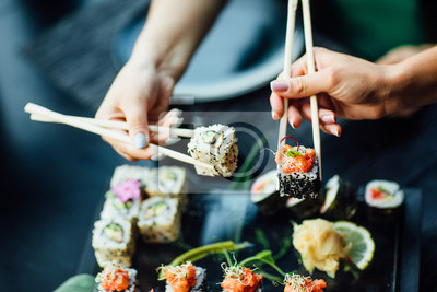 Fototapeta Chopstick holding sushi rolls set with salmon and cream cheese and cuccumber on black plate. Close Up. Uramaki, nori maki or futomaki sushi with trout fillets, soy sauce and wasabi.