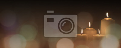 Fototapeta Christmas advent candle light in church with blurry golden bokeh for religious ritual or spiritual zen meditation, peaceful mind and soul, or funeral ceremony