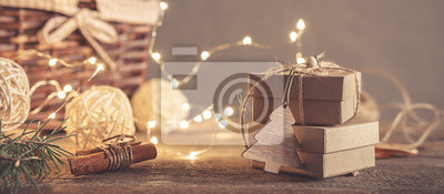 Fototapeta Christmas and zero waste, eco friendly packaging gifts in kraft paper on a wooden table, eco christmas holiday concept, eco decor banner