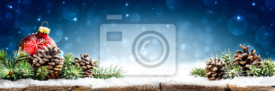 Fototapeta Christmas - Banner Of Red Ornament, Pine-cones And Branches On Snowy Wooden Table With Blue Bokeh Background