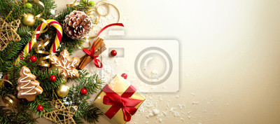 Fototapeta Christmas decoration composition on light gold background with beautiful Golden gift box with red ribbon, fir branches, cones, stars, Christmas cookies,cinnamon, top view, copy space, banner format.