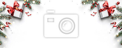 Fototapeta Christmas fir branches, gift boxes with red ribbon, red decoration, sparkles and confetti on white background. Xmas and New Year greeting card, winter holiday. Flat lay, top view