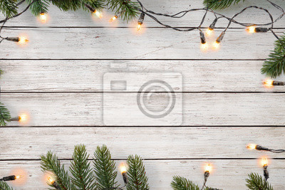 Fototapeta Christmas lights bulb and pine leaves decoration on white wood plank, frame border design. Merry Christmas and New Year holiday background. top view.