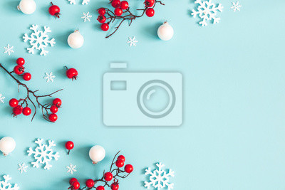 Fototapeta Christmas or winter composition. Snowflakes and red berries on blue background. Christmas, winter, new year concept. Flat lay, top view, copy space