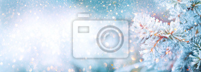 Fototapeta Christmas winter blurred background. Xmas tree with snow decorated with garland lights, holiday festive background. Widescreen backdrop. New year Winter art design, wide screen holiday border