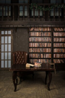 Fototapeta Classical library room with leather armchair, wooden table and bookcase..