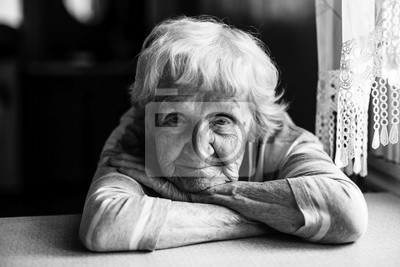 Fototapeta Close-up black and white portrait of a old woman at the table in home.