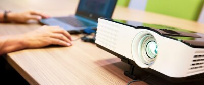 Fototapeta Close up computer projector on meeting tables with technician setup laptop at boardroom or seminar or classroom for conference presentation visual multimedia presenting concepts.