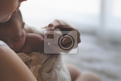 Fototapeta Close up Mother holding hands Asian female newborn baby  and sunlight in the morning. Cute little girl  three weeks old. Health, care, love, relationship concept.