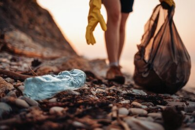 Fototapeta Close up of blue plastic bottle lying on the beach. Close up of volunteer's hands with plastic bag picks up a bottle. The concept of Earth Day and envinmental pollution
