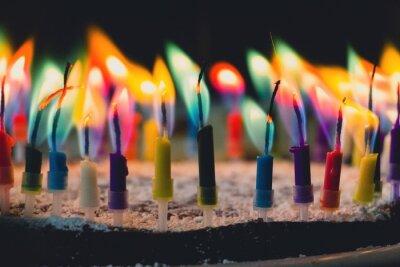 Fototapeta Close-Up Of Colorful Candles Burning On Birthday Cake