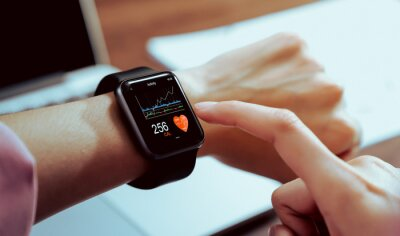 Fototapeta Close up of hand touching smartwatch with health app on the screen, gadget for fitness active lifestyle.