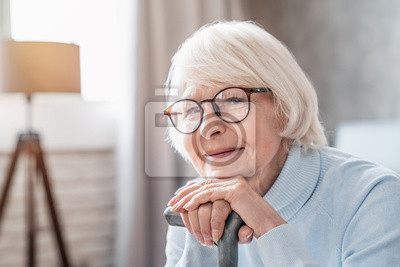 Fototapeta Close up of mature woman in glasses holding cane while sitting on sofa at home
