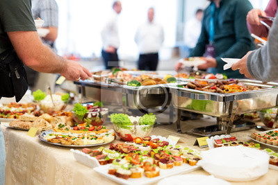Fototapeta Close up of people serving themselves with canapes in buffet of restaurant.