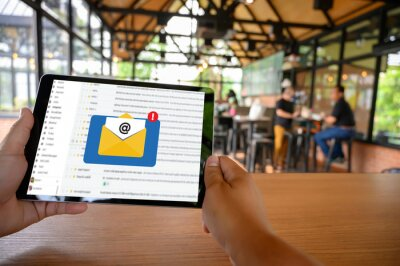 Fototapeta Close-up Of Person Holding Digital Tablet With Mails At Restaurant