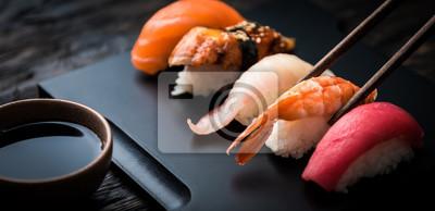 Fototapeta close up of sashimi sushi set with chopsticks and soy on black background