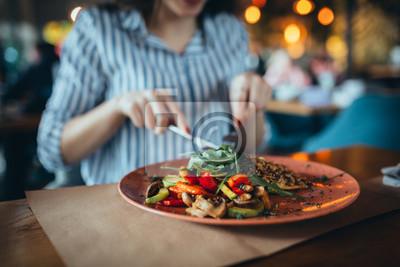 Fototapeta close up of woman in restaurant eating