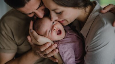 Fototapeta Close up of young parents holding and kissing their newborn baby indoors at home