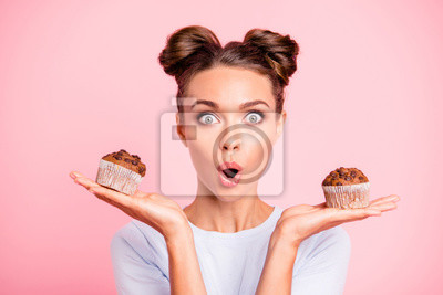 Fototapeta Close-up portrait of nice lovely cute attractive amazed scared afraid girl holding in hands two cakes choosing deciding dilemma opened mouth isolated over pink pastel background
