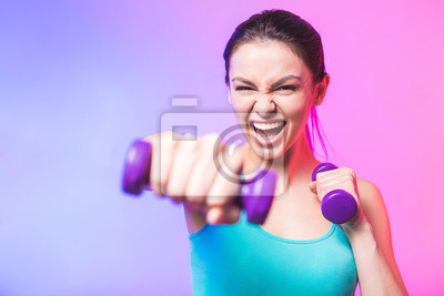 Fototapeta Close-up portrait of young attractive happy woman in sport clothes with beautiful smile holding weight dumbbell doing fitness workout isolated on white background in healthy lifestyle concept