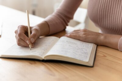 Fototapeta Close up view of millennial woman sit at table hold pencil take notes to paper notebook working studying. Female student businesswoman employee write records to daily planner by hand at home work desk