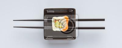 Fototapeta Close-up widok smaczne sushi i pałeczki na białym