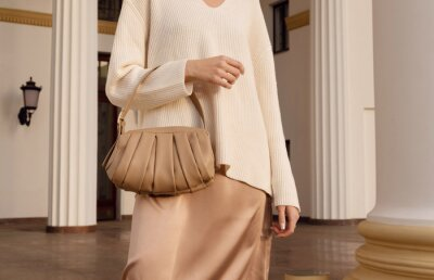 Fototapeta Closeup beige leather bag in hand of fashion woman in silk skirt. Elegant fall and spring outfit.
