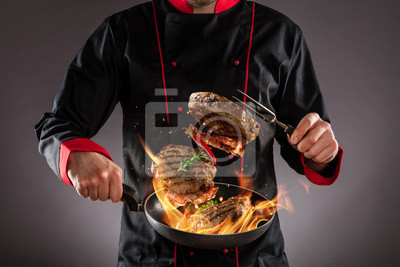 Fototapeta Closeup of chef throwing beef steaks into the air