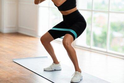 Fototapeta Closeup Of Woman In Black Sportswear Exercising With Elastic Band