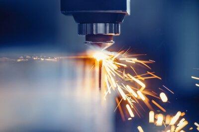 Fototapeta CNC gas cutting metal sheet, sparks fly. Blue steel color, modern industrial technology