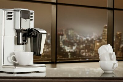 Coffee machine in office and blurred window of city at night