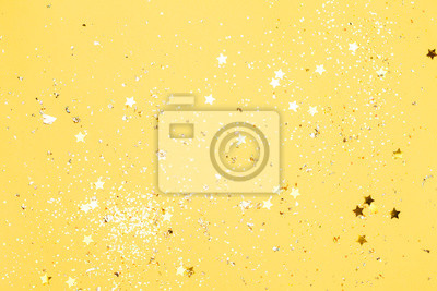 Fototapeta Colorful yellow confetti background. Vibrant and holiday. Top view, flat lay.