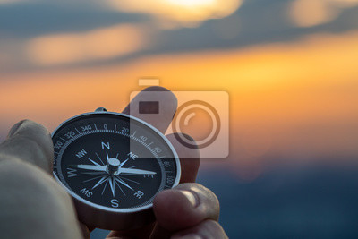 Fototapeta compass in hand with sunset sky on the background