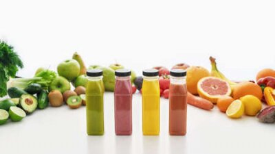 Fototapeta Composition of bottles of healthy detox juices and smoothies with various colorful fruits and vegetables isolated over white background
