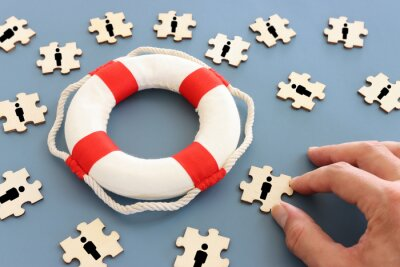 Fototapeta Concept image of life buoy protecting group of people. Rescue and support in times of crisis metaphor
