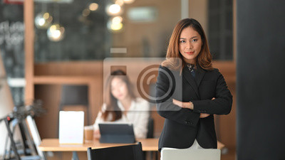 Fototapeta Confidently  asian businesswoman standing on front of office workplace.
