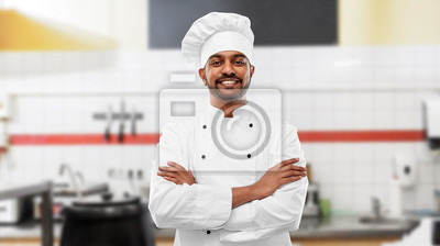 Fototapeta cooking, profession and people concept - happy male indian chef in toque with crossed arms over restaurant kitchen background