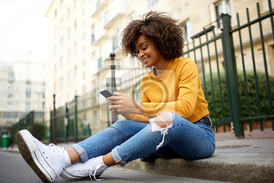 Fototapeta cool young african american woman sitting outside on street with cellphone