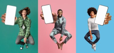 Fototapeta Cool young guys with empty smartphones jumping up in air over colorful studio backgrounds, mobile application mockup