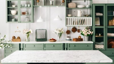 Fototapeta Countertop with green vintage kitchen furniture in blurred background