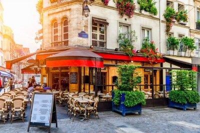 Fototapeta Cozy street with tables of cafe in Paris, France. Architecture and landmark of Paris. Cozy Paris cityscape.