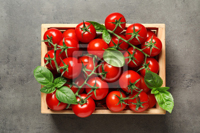 Fototapeta Crate with fresh cherry tomatoes on stone background, top view