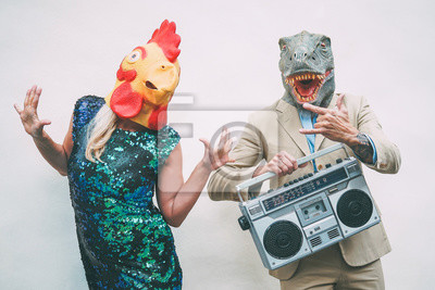Fototapeta Crazy senior couple wearing chicken and t-rex mask while dancing outdoor - Mature trendy people having fun celebrating and listening music with boombox - Absurd concept of masquerade funny holidays