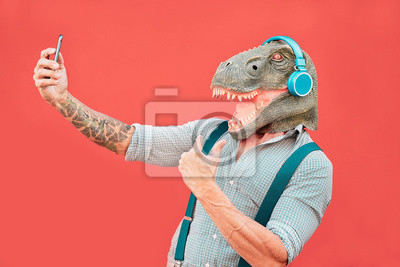 Fototapeta Crazy senior man wearing t-rex mask and taking selfie with mobile smartphone - Hipster older male having fun listening music and dancing outdoor -  Absurd, funny and surreal concepts