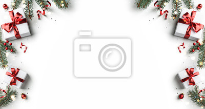 Fototapeta Creative frame made of Christmas fir branches, gift boxes, red decoration, sparkles and confetti on white background. Xmas and New Year holiday, bokeh, light. Flat lay, top view
