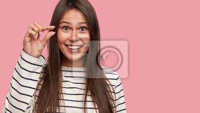 Fototapeta Cropped strzał z radością ciemnych włosach młoda kobieta pokazuje bardzo małe, gesty ręką, ubrany w ubranie, pozy na różowym tle z wolnego miejsca na promocję. Słuchaj, jest za mały