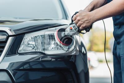 Fototapeta cropped view of car cleaner polishing headlamp with polish machine