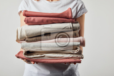 Fototapeta Cropped view of woman holding folded ironed clothes isolated on grey