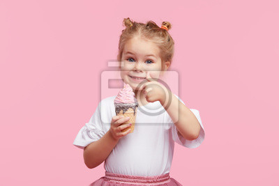 Fototapeta Cute child girl with pleasure eats tasty ice-cream on a pink studio background. Licks with closed eyes. The concept of baby food and a happy childhood